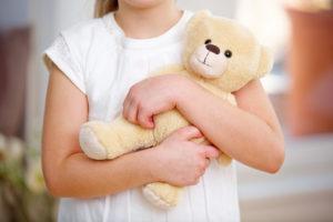 child holding stuffed bear