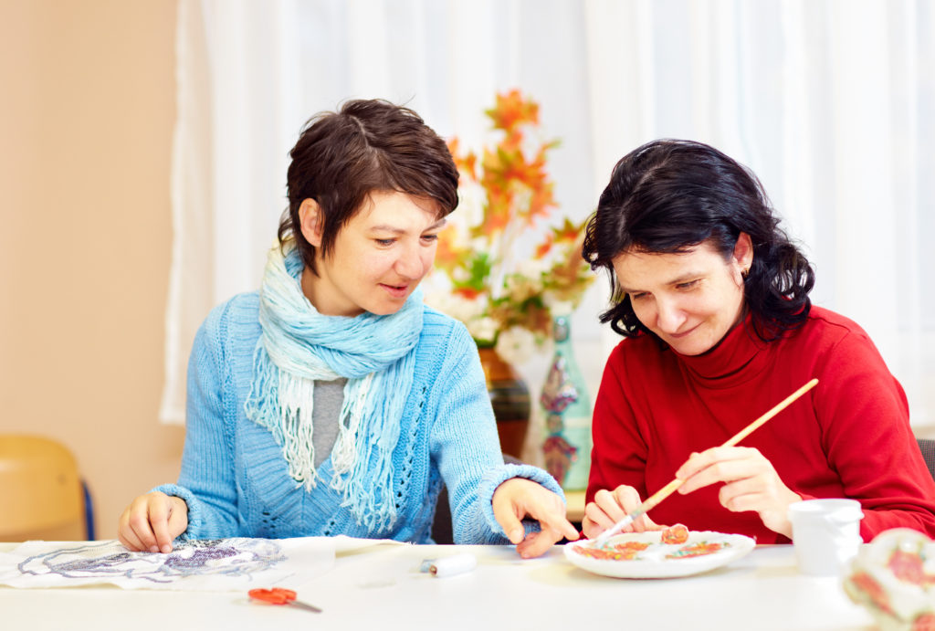 adult woman with special needs are engaged in handcraft in rehabilitation center