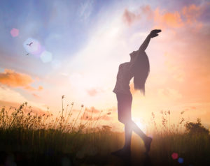 World environment day concept: Silhouette of healthy woman raised hands for praise and worship God at sunset meadow background.
