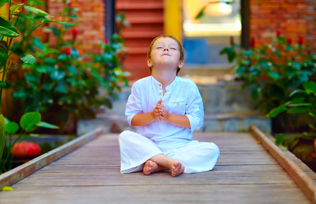 cute boy trying to find inner balance in self-care meditation